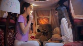 Dwa siostry siedzi pod koc przy sypialnią i mówi opowieści z latarką zbiory