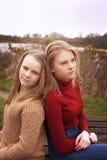 Dwa siostry siedzi z powrotem popierać Zdjęcie Royalty Free