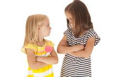 Dwa siostry z rękami składali gniewny patrzeć each Fotografia Stock