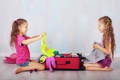 Dwa siostry zbierają walizkę na podróży Zdjęcia Royalty Free