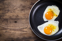 Dwa smażą jajka w niecce na stole Zdjęcie Royalty Free