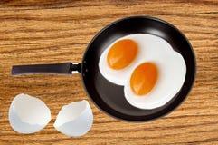 Dwa smażyli jajka na niecce na drewnianym stołowym tle Obraz Royalty Free