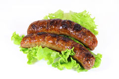 Dwa smakowita piec na grillu kiełbasa z sałatą Zdjęcia Stock