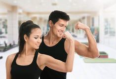 Dwa sportive trenera w czerni pokazuje bicepsy Fotografia Stock