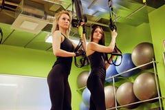 Dwa sporty kobiety robi trx troczą ćwiczenia w gym zdjęcia stock