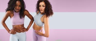 Dwa sprawności fizycznej kobiety w sportswear odizolowywającym nad szarym tłem Sporta i mody pojęcia dowcipu chopy przestrzeń zdjęcie royalty free