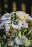 Dwa srebnej obrączki ślubnej z klejnotami na śmietankowych różach poślubia bouqu obraz royalty free