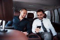 Dwa starego biznesowego przyjaciela wnioskują nową zgodę w nieformalnym położeniu w samochodu wnętrzu obraz royalty free