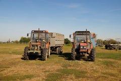 Dwa starego ciągnika z przyczepami na polu Na gospodarstwie rolnym fotografia stock