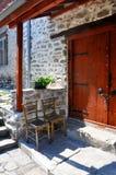 Dwa starego krzesła stoi pod baldachimem blisko drewnianego drzwi drylują dom Obrazy Stock