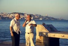 Dwa starego mężczyzna na molu z Lisbon w tle Fotografia Stock