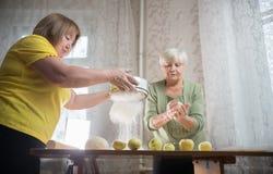 Dwa starsza kobieta robi jabłczanym małym kulebiakom w domu Odsiew mąka na stole zdjęcia royalty free