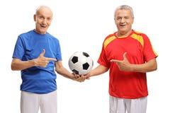 Dwa starszego gracza piłki nożnej trzyma wskazywać i futbol Obraz Stock