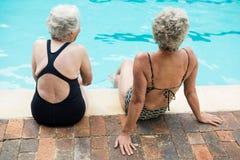 Dwa starszej kobiety siedzi wpólnie przy poolside obrazy stock