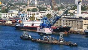 Dwa statku holują żurawia na dennej zatoce zbiory