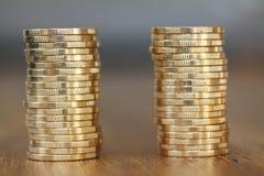 Dwa sterty złocista pieniądze monet moneta w stosie na zamazanym tle obrazy royalty free