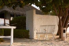 Dwa stołu z listą usługa blisko zdroju i krzesła ześrodkowywają bungalowu wejście na tropikalnej wyspie w Maldives przy egzotem Zdjęcia Stock