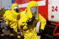 Dwa strażaka w ochronnych kostiumach i maskach gazowych przygotowywają dla pracy zdjęcie stock