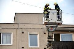 Dwa strażaków uprise w teleskopowego huku kosz samochód strażacki, blok mieszkalny w tle Fotografia Royalty Free