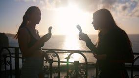 Dwa sylwetki młode opowiada kobiety stoi na quay i je lody na zmierzchu zdjęcie wideo