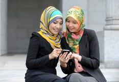 Dwa szalików dziewczyna używa mądrze telefon obrazy royalty free