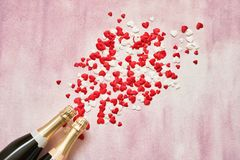 Dwa szampańskiej butelki z czerwonymi i białymi sercami na różowym tle Odbitkowa przestrzeń, odgórny widok zdjęcie stock