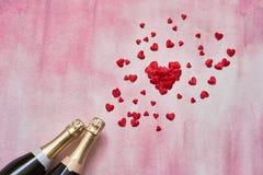 Dwa szampańskiej butelki z czerwonymi sercami na różowym tle Odbitkowa przestrzeń, odgórny widok, mieszkanie nieatutowy walentynk obrazy royalty free