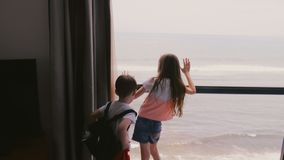 Dwa szczęśliwego z podnieceniem małego dziecka biega do wielkiego hotelowego mieszkania okno cieszyć się nieprawdopodobnego chmur zbiory