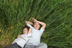 Dwa szczęśliwa chłopiec kłaść w trawie Obraz Stock