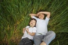 Dwa szczęśliwa chłopiec kłaść w trawie Zdjęcie Royalty Free