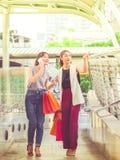 Dwa szczęśliwa młoda kobieta trzyma torba na zakupy w mieście Fotografia Royalty Free