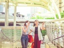 Dwa szczęśliwa młoda kobieta trzyma torba na zakupy w mieście Obrazy Royalty Free