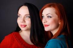 dwa szczęśliwe dziewczyny Czarny tło fotografia stock