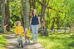 Dwa szczęśliwego brata w żółtych bluzach sportowa w jesień parku Zdjęcia Royalty Free