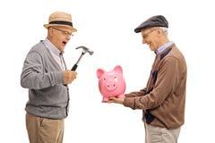 Dwa szczęśliwego dojrzałego mężczyzna przygotowywa łamać piggybank z hamme Zdjęcia Stock