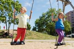 Dwa szczęśliwego dzieciaka huśta się na huśtawce przy boiskiem Zdjęcie Stock