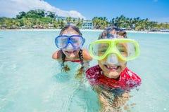 Dwa szczęśliwego dzieciaka w pikowanie maskach ma zabawę na plaży Obraz Stock
