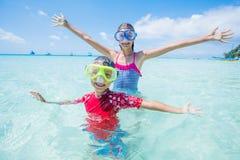 Dwa szczęśliwego dzieciaka w pikowanie maskach ma zabawę na plaży Zdjęcia Royalty Free