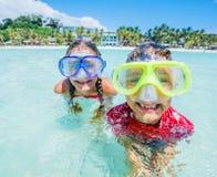 Dwa szczęśliwego dzieciaka w pikowanie maskach ma zabawę na plaży Fotografia Stock