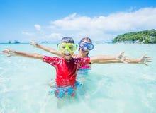 Dwa szczęśliwego dzieciaka w pikowanie maskach ma zabawę na plaży Fotografia Royalty Free
