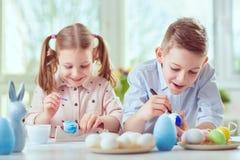 Dwa szczęśliwego dziecka ma zabawę podczas obrazów jajek dla Easter wewnątrz Fotografia Stock