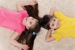 Dwa szczęśliwego dziecka na białym dywanie obraz stock