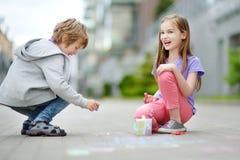 Dwa szczęśliwego dziecka rysuje z kolorowym piszą kredą na chodniczku Lato aktywność dla małych dzieciaków Obrazy Stock