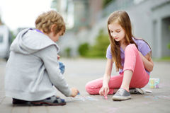Dwa szczęśliwego dziecka rysuje z kolorowym piszą kredą na chodniczku Lato aktywność dla małych dzieciaków Fotografia Royalty Free