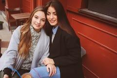 Dwa szczęśliwego dziewczyna przyjaciela opowiada kawę w jesieni mieście w kawiarni i pije zdjęcia stock