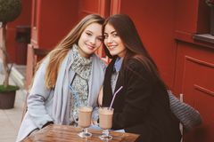 Dwa szczęśliwego dziewczyna przyjaciela opowiada kawę w jesieni mieście w kawiarni i pije Spotkanie dobrzy przyjaciele, młodzi mo zdjęcia royalty free