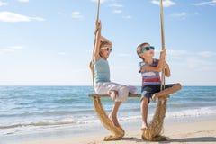 Dwa szczęśliwego małego dziecka bawić się na plaży przy dnia czasem Zdjęcie Royalty Free