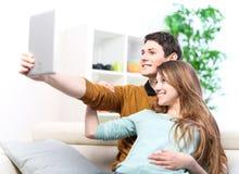 Dwa szczęśliwego przyjaciela bierze fotografię z pastylka komputerem osobistym na cou w domu Obrazy Royalty Free