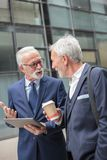Dwa szczęśliwego starszego szarego włosianego biznesmena chodzi wzdłuż ulicy podczas kawowej przerwy fotografia royalty free
