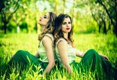 Dwa szczęśliwej ładnej dziewczyny siedzi na zielonej trawie Fotografia Royalty Free